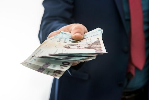 Biznesmen w odosobnieniu daje łapówkę lub zapłatę. uah. 1000 nowych banknotów ukraińskich pieniędzy