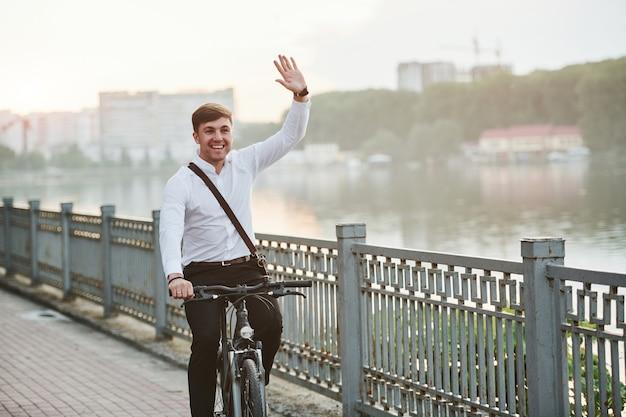 Biznesmen w oficjalnych ubraniach z czarnym rowerem jest w mieście.