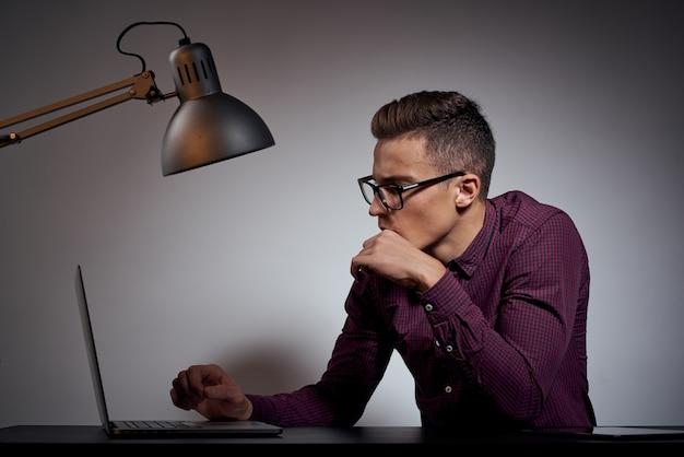 Biznesmen w okularach i koszuli siedzi przy stole z otwartymi laptopami coffee space telefon komórkowy.