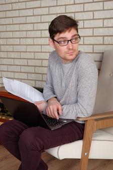 Biznesmen w okularach pracuje na laptopie z dokumentami roboczymi.