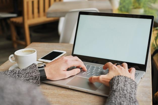 Biznesmen w okularach siedzi przy stole w kawiarni z laptopa podczas korzystania ze smartfona