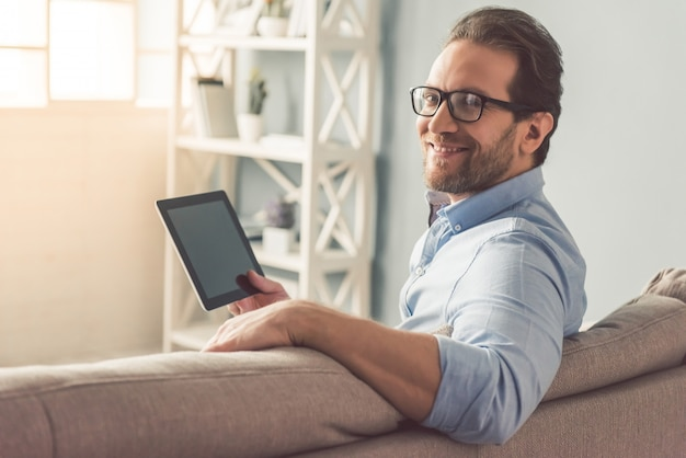 Biznesmen w okularach używa cyfrowej tabletki.