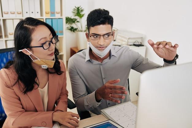Biznesmen w okularach wyjaśniający szefowi działu rozmowy na ekranie komputera, dzieli się też swoimi pomysłami na rozwój firmy