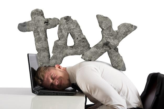 Biznesmen w pracy ze swoim laptopem jest uciskany ciężarem podatków