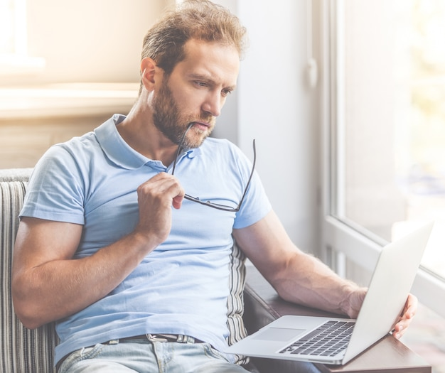 Biznesmen w przypadkowych ubraniach używa laptop