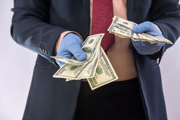 Biznesmen w rękawice ochronne z pieniędzmi na białym tle. koncepcja medyczna covid 19 koronawirus