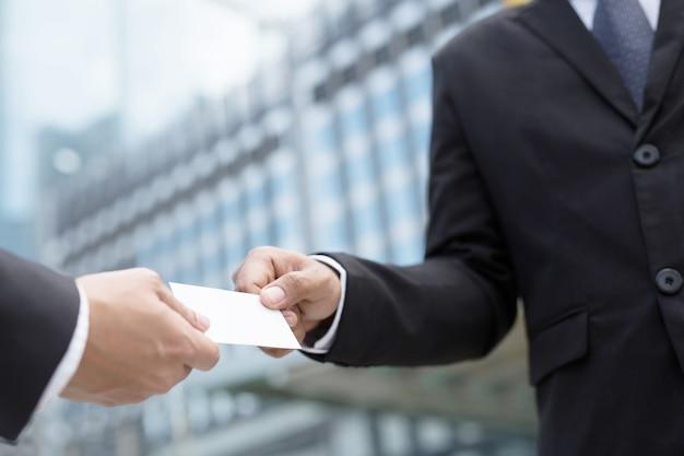Biznesmen w ręku trzymaj pokaż wizytówki pusta biała karta makieta zgłoszenia