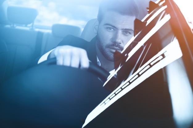 Biznesmen w samochodzie widok z tyłu młody przystojny mężczyzna patrząc na t