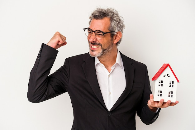 Biznesmen w średnim wieku gospodarstwa rachunki i model domu na białym tle na niebieskim tle podnosząc pięść po zwycięstwie, koncepcja zwycięzca.