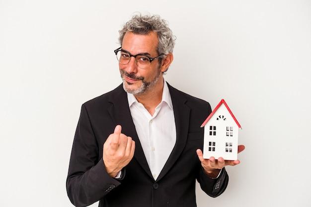 Biznesmen w średnim wieku gospodarstwa rachunki i model domu na białym tle na niebieskim tle wskazując palcem na ciebie, jakby zapraszając zbliżyć się.