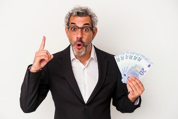 Biznesmen w średnim wieku gospodarstwa rachunki na białym tle na niebieskim tle o pomysł, koncepcja inspiracji.