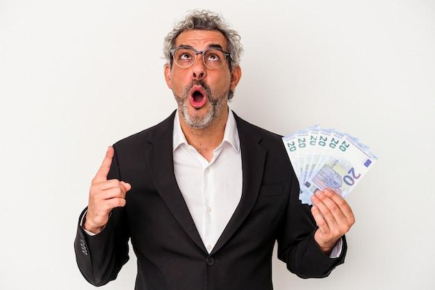 Biznesmen w średnim wieku gospodarstwa rachunki na białym tle na niebieskim tle, wskazując do góry z otwartymi ustami.