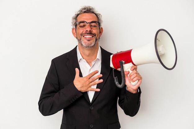 Biznesmen w średnim wieku posiadający megafon na białym tle śmieje się głośno trzymając rękę na klatce piersiowej.