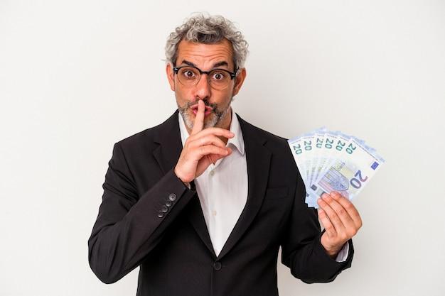 Biznesmen w średnim wieku posiadający rachunki na białym tle na niebieskim tle dochowując tajemnicy lub prosząc o ciszę.