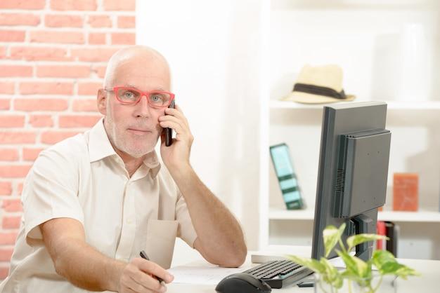 Biznesmen w średnim wieku siedzi przy biurku rozmawia przez telefon komórkowy