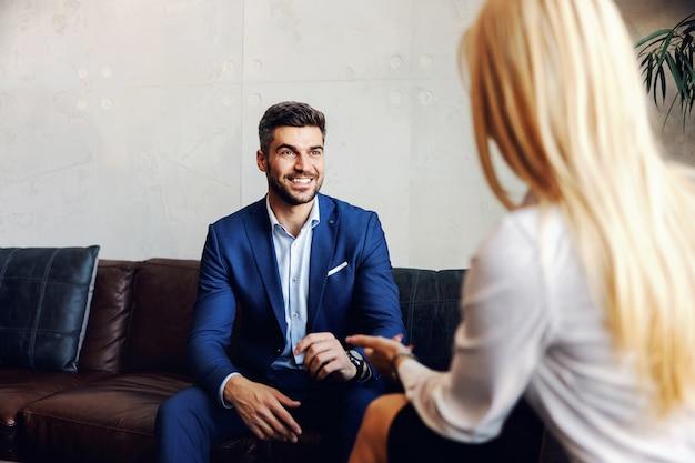 Biznesmen w średnim wieku siedzi w holu z kobietą ceo na rozmowie kwalifikacyjnej.