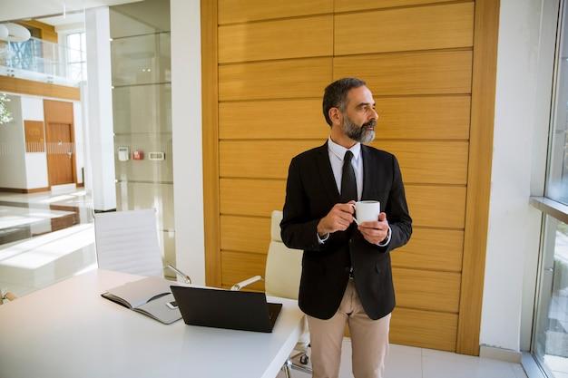 Biznesmen w średnim wieku trzyma filiżankę kawy lub w biurze