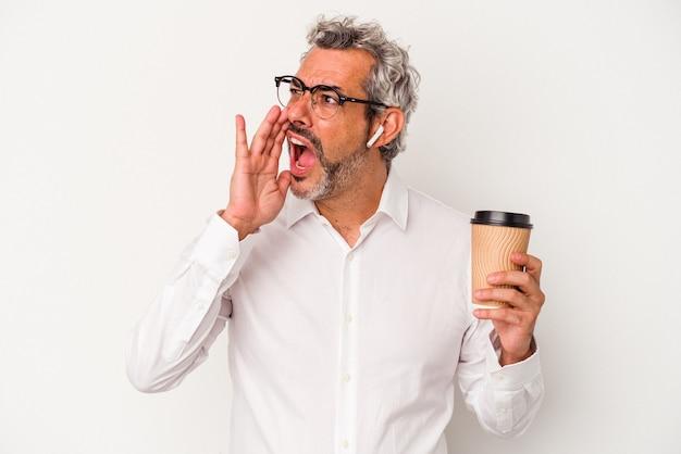 Biznesmen w średnim wieku trzyma kawę na wynos na białym tle krzycząc i trzymając dłoń w pobliżu otwartych ust.
