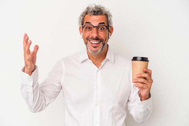 Biznesmen w średnim wieku trzymając kawę na wynos na białym tle otrzymujący miłą niespodziankę, podekscytowany i podnoszący ręce.