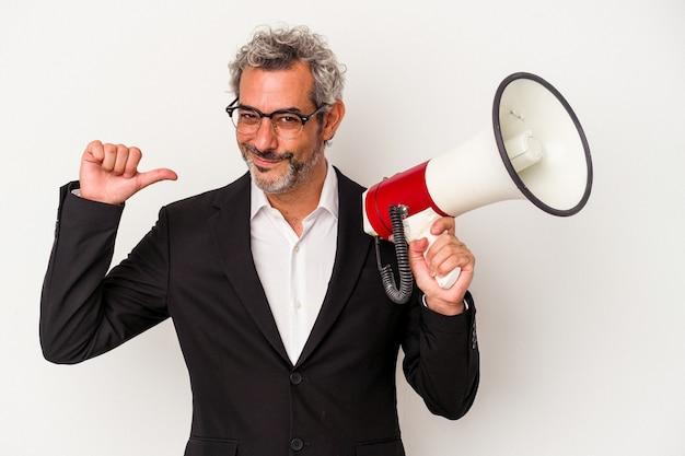 Biznesmen w średnim wieku trzymający megafon na białym tle czuje się dumny i pewny siebie, przykład do naśladowania.