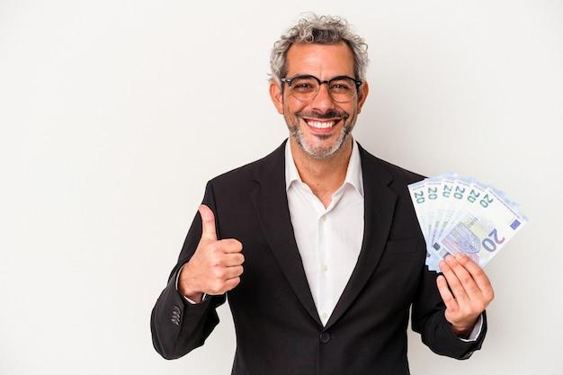 Biznesmen w średnim wieku trzymający rachunki na białym tle na niebieskim tle, uśmiechający się i unoszący kciuk w górę