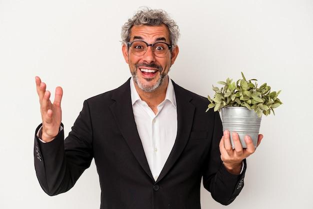 Biznesmen w średnim wieku trzymający roślinę na białym tle otrzymujący miłą niespodziankę, podekscytowany i podnoszący ręce.