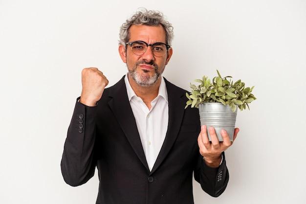 Biznesmen w średnim wieku trzymający roślinę na białym tle pokazujący pięść do kamery, agresywny wyraz twarzy.
