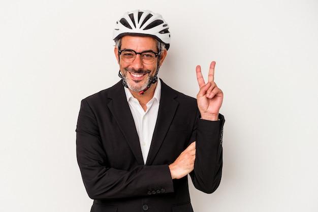 Biznesmen w średnim wieku ubrany w kask rowerowy na białym tle na niebieskim tle pokazując numer dwa palcami.