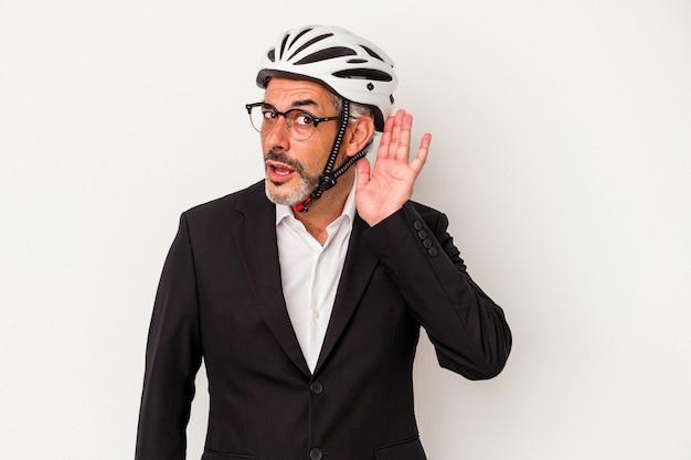 Biznesmen w średnim wieku ubrany w kask rowerowy na białym tle na niebieskim tle próbuje słuchać plotek.
