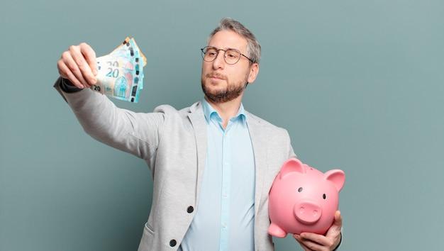 Biznesmen w średnim wieku z pieniędzmi i skarbonką