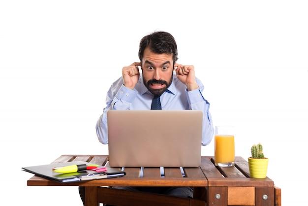 Biznesmen w swoim biurze, obejmuj? c uszy