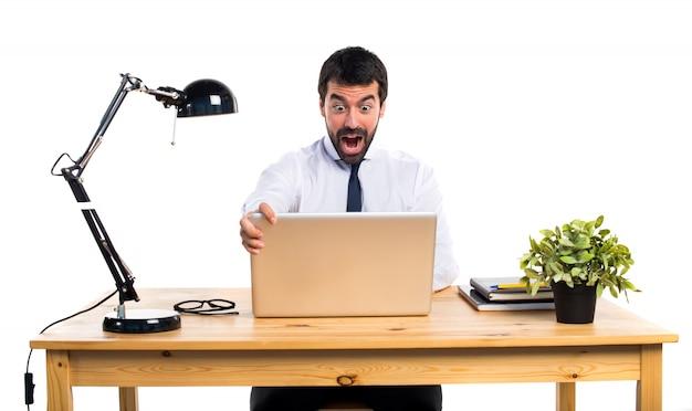 Biznesmen w swoim biurze robi gest niespodzianka