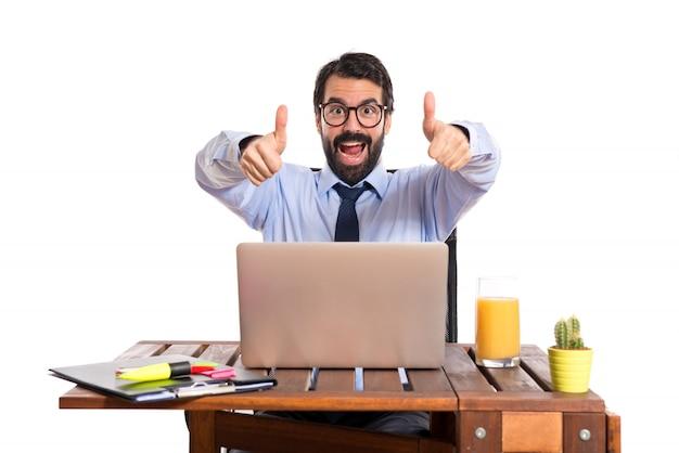 Biznesmen w swoim biurze z kciukiem do góry