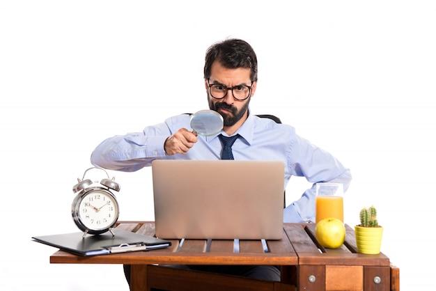 Biznesmen w swoim biurze z lupą
