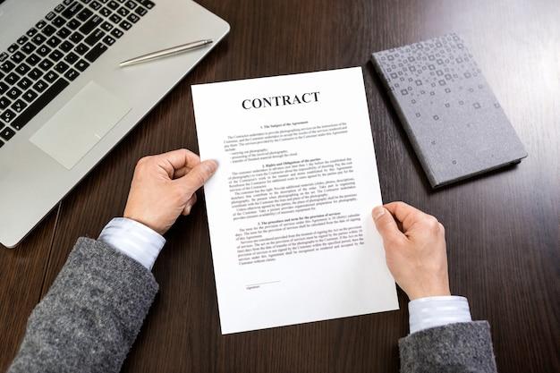 Biznesmen w szarym kolorze, czytanie dokumentów umowy na biurku w biurze