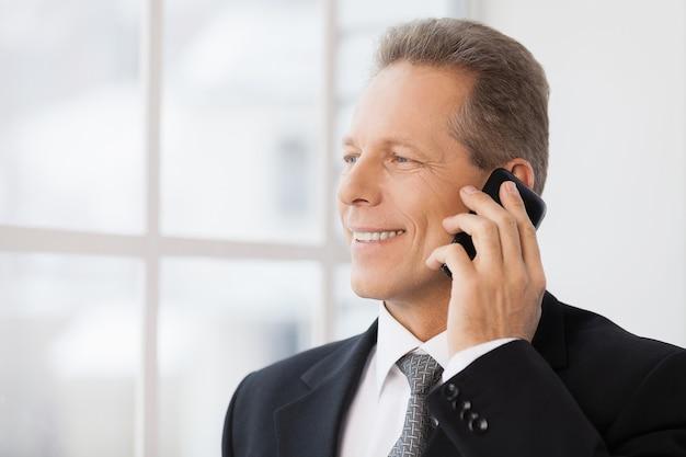 Biznesmen w telefonie. portret wesołego dojrzałego mężczyzny w formalnej odzieży, rozmawiającego przez telefon i uśmiechającego się, stojąc w pobliżu okna