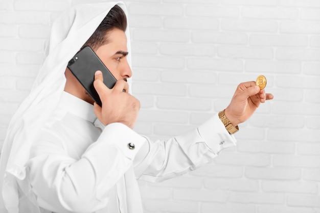 Biznesmen w tradycyjnym stroju wygląda na złotym bitcoinie