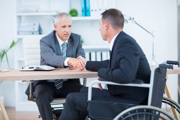 Biznesmen w wózku inwalidzkim trząść ręki z kolegą