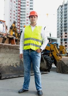 Biznesmen w żółtej kurtce ochronnej i kasku pozuje obok buldożera