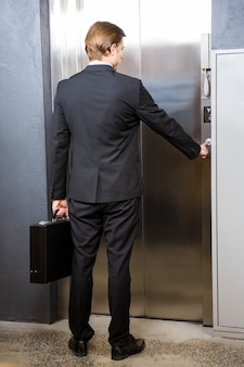 Biznesmen windy naciskowy guzik w biurze
