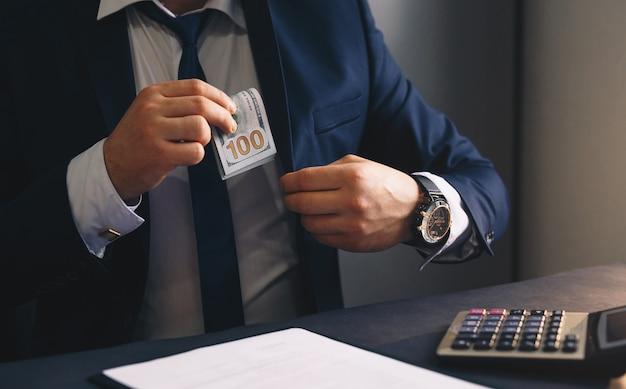 Biznesmen wkłada banknoty dolarów do kieszeni garnituru