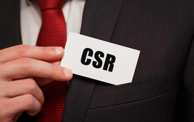 Biznesmen wkłada do kieszeni kartę z tekstem csr
