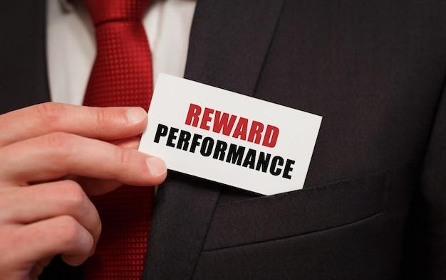 Biznesmen wkłada do kieszeni kartę z tekstem nagroda wydajność