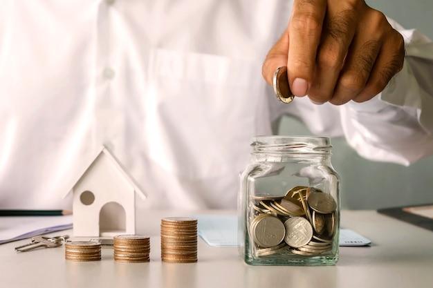 Biznesmen wkłada pieniądze do butelki oszczędnościowej i modelu domu