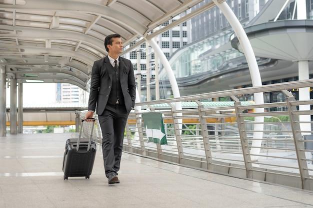 Biznesmen wlec walizkę na moscie