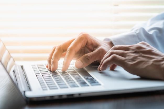 Biznesmen, wpisując na klawiaturze laptopa i jedną ręką na touchpad. pomysł na biznes.