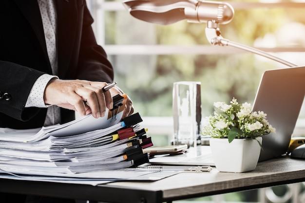 Biznesmen wręcza mienia pióro dla pracować w stertach papierowe kartoteki