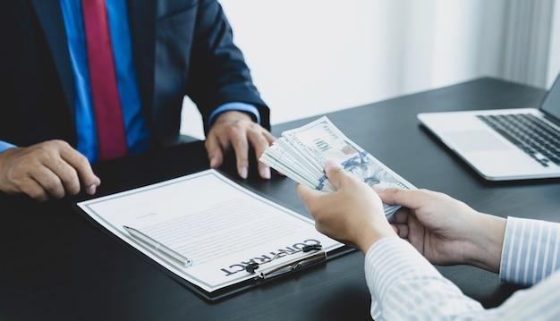 Biznesmen wręcza pieniądze, aby urzędnik państwowy podpisał umowę
