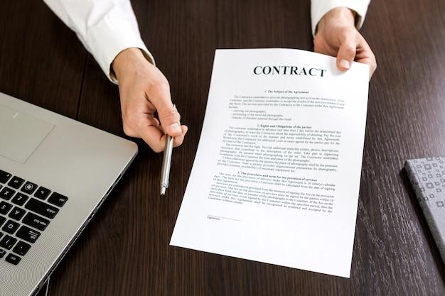 Biznesmen wręczanie umowy do podpisu, oferując w ręku srebrny długopis.