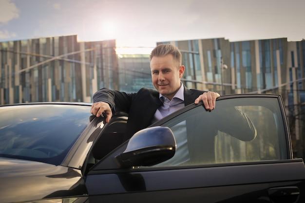 Biznesmen wsiada do swojego samochodu